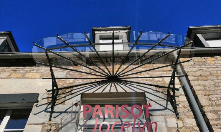 Marquise arrondie de grande longueur fer forgé sur façade pierre de taille en centre ville de Vesoul, conception et pose Métallerie PARISOT Jocelyn Vesoul